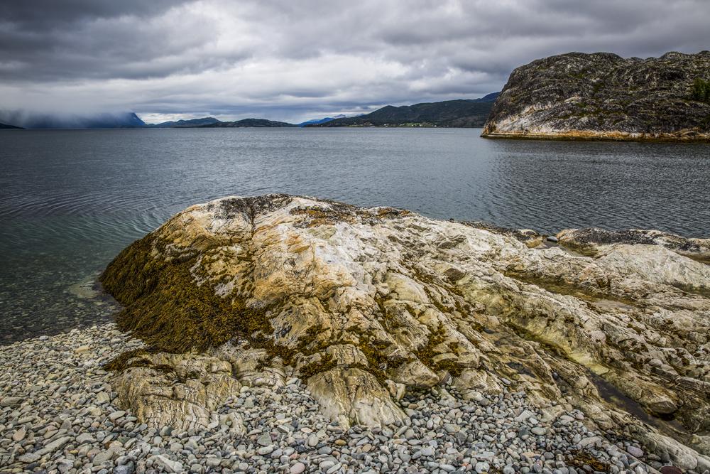 Vackra stenformationer i förgrunden med vackra molnbeklädda berg i bakgrunden