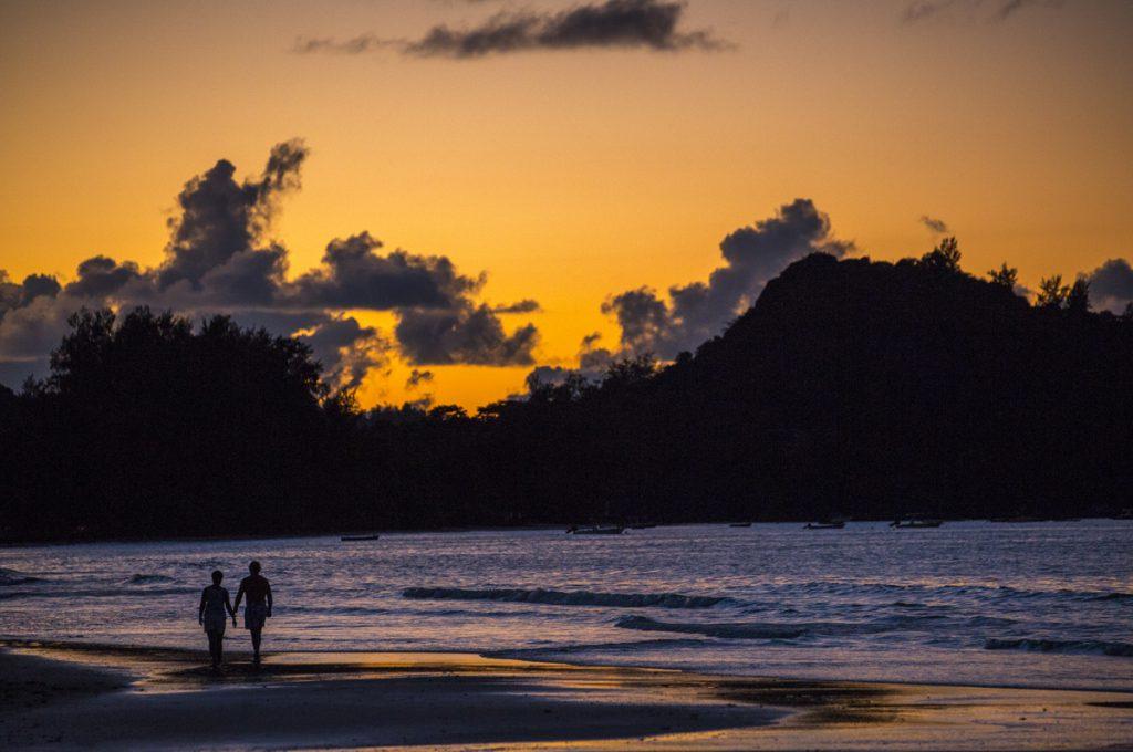 Ett förälskat par promenerar på Anse Volbert i skymningsljuset