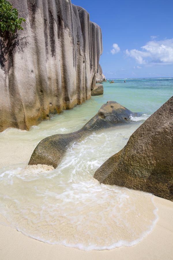 Det turkosa vattnet sköljer in över stranden mellan klippblocken