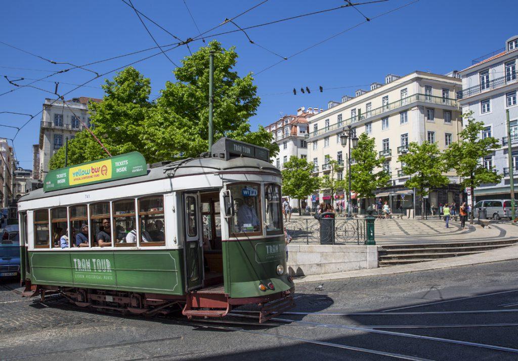 Spårvagn - grön linje, vid Torget Praça Luís de Camões. Ska den ta spåret till höger eller spåret till vänster? Vad pratar duvorna på tråden om?