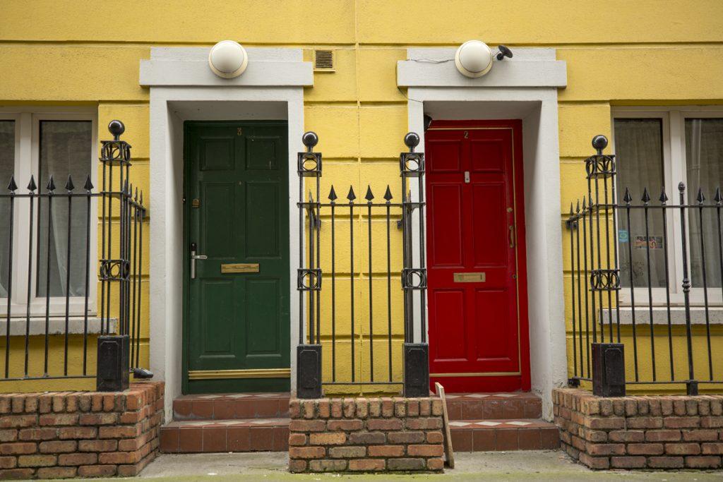 Två färglada dörrar på ett gult hus