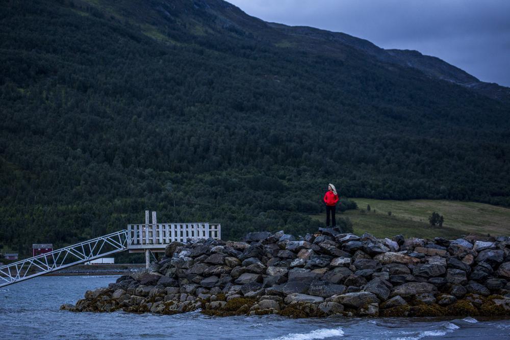 Ylva i röd jacka lyser upp molniga Altafjorden