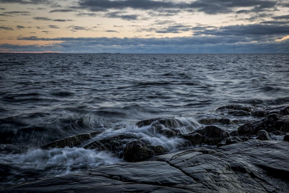 Vågor slår över stenarna och bildar vackra mönster