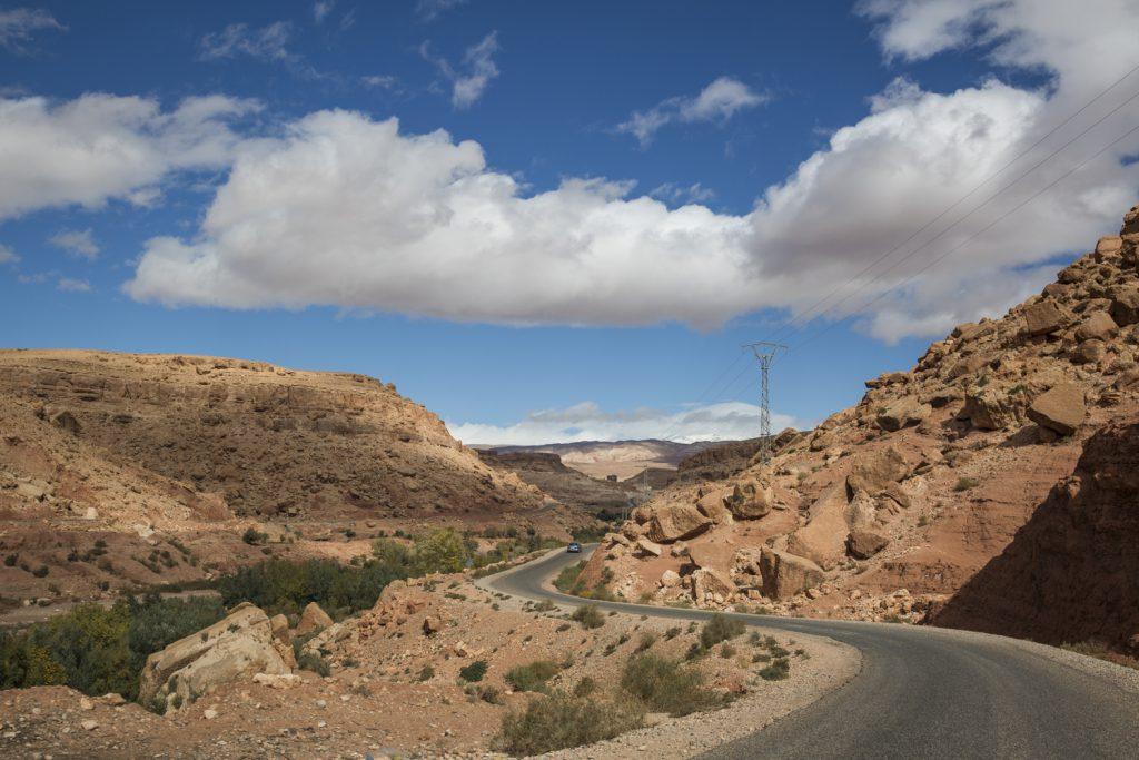 Vägen slingrar sig genom häftiga landskap i Atlasbergen. Stenblocken vilar hotfullt på sluttningarna