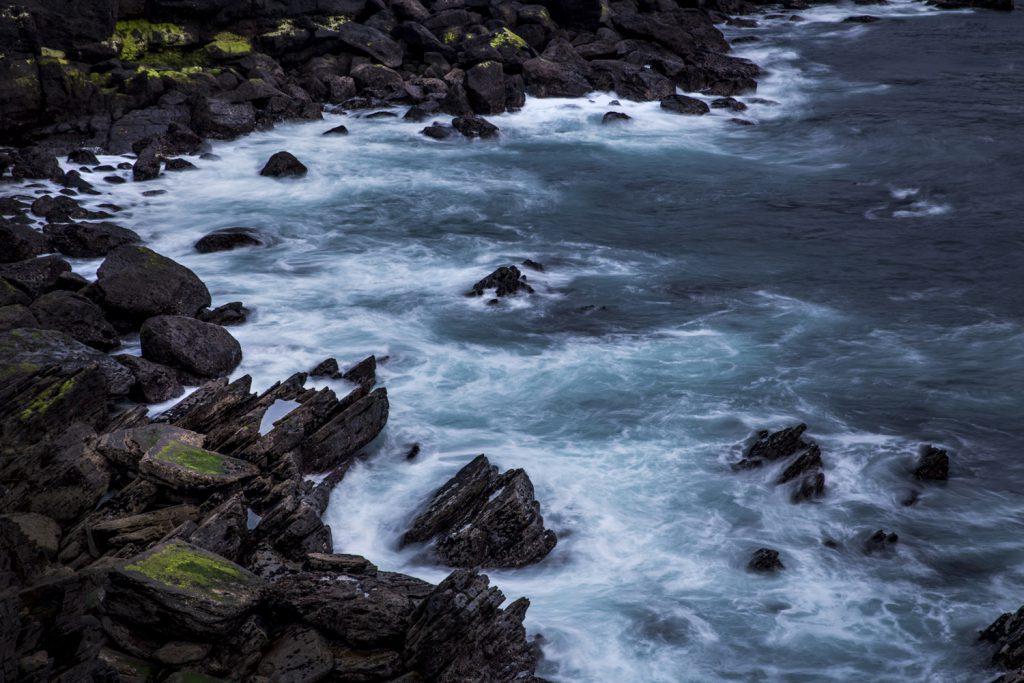 Vågorna virvlar runt de sylvassa klipporna