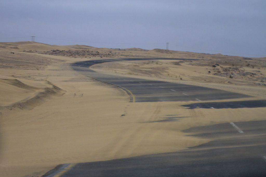 Sanden blåser in över vägen som innehåller kurvor, sista biten på väg till hamnstaden Luderitz