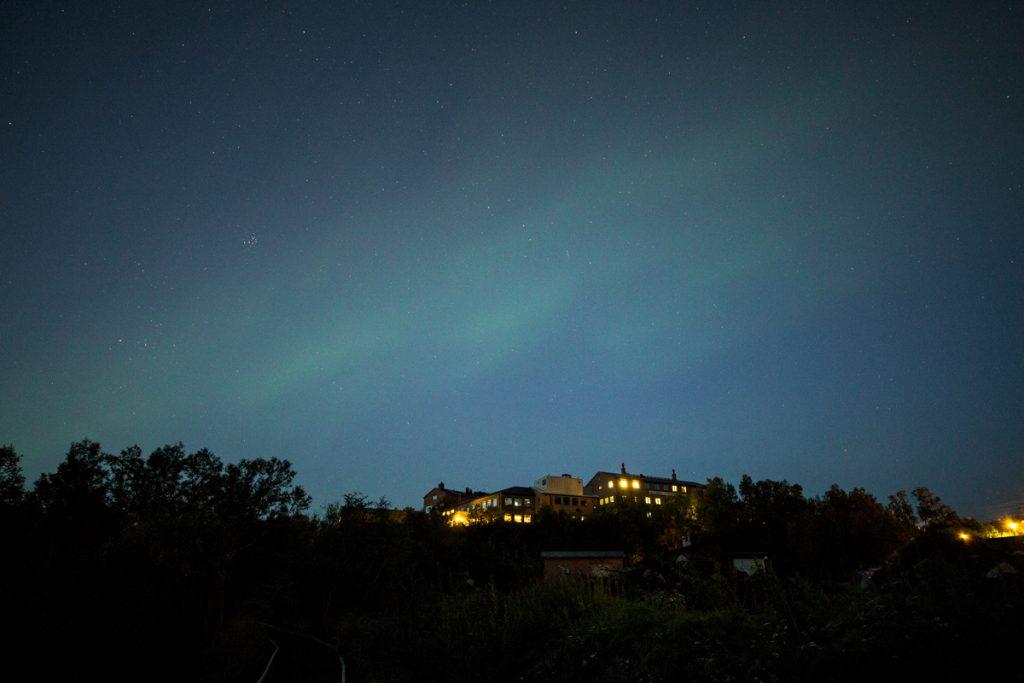 Ett försiktigt Norrsken dansar på himlen en klar natt över turisthotellet i Abisko